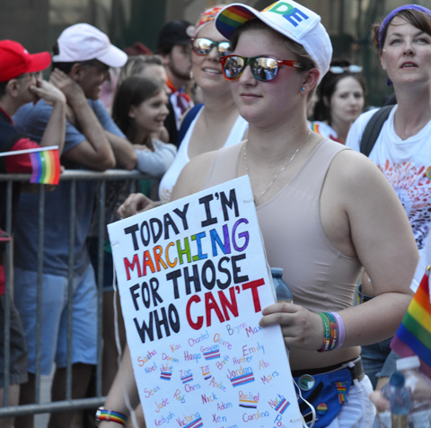 a person walking the pride parade carrying a sign that says I am marching for those who can't