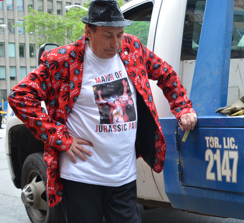 a man in black fedora andred jacket with raptors symbols all over it, and a t shirt that says Mayor of Jurassic Park, leans against a tw truck, head down, not smiling