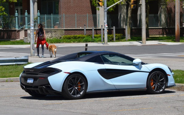 pale blue and black mclaren car parked in a parking lot, woman with dog in the background