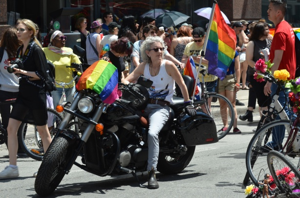 a woman sits on a motorcycle waiting for the dyke march to begin