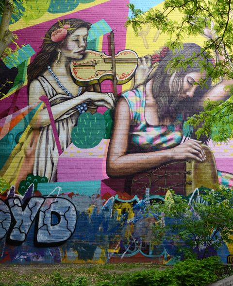 violin player in mural along with woman playing a drum with her eys closed and head bent forward