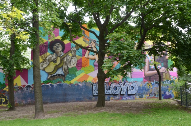 large mural on the side of a building beside green space, with a couple of trees in front