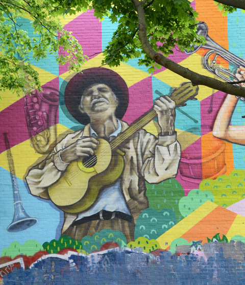 part of a mural by Jieun June Kim, Pablo West, and Giovanni Zamora, a male guitar player, with large brim hat, on background made of multicoloured cubes on point