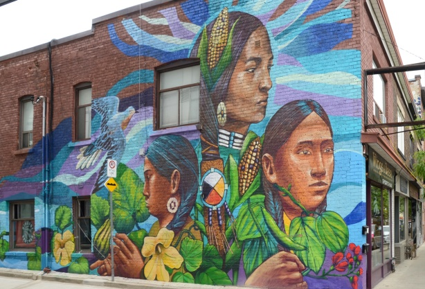 large mural by street artists tikay and aner on Dundas West, 3 indigenous women in traditional clothes with symbols, corn, squash, medicine wheel, flowers,
