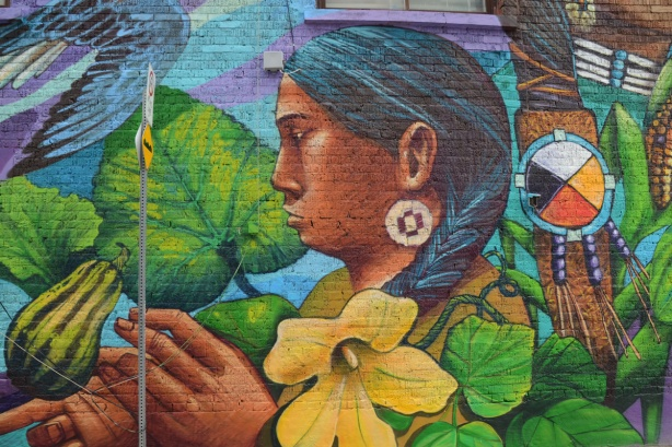 close up of woman with long black braided hair, standing in the midst of a squash plant, with yellow flower, a squash, and many leaves, in mural