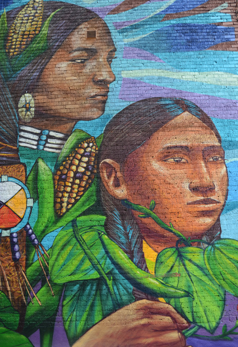 close up of two women in mural with cobs of corn and alarge green bean growing on a bean plant, lots of leaves