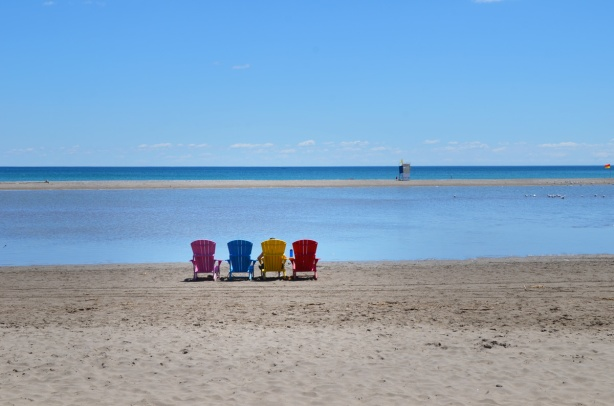 4 muskoka chairs lined up on the beach, pink, blue, yellow, and red, lots of water, a person is sitting in one of them but photo is of back of chairs.