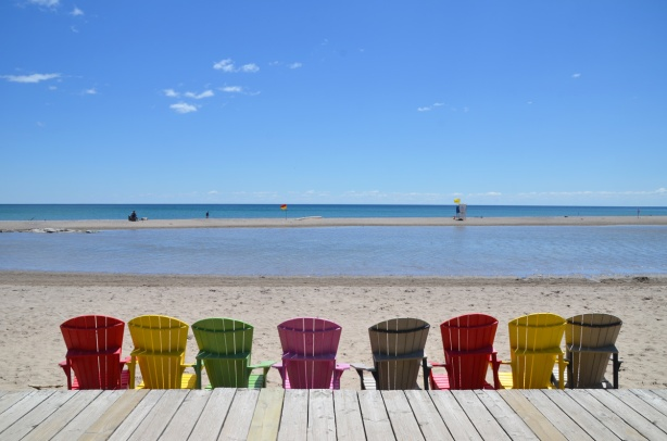 a line of muskoka chairs along the edge of the boardwalk, beach, Lake Ontario