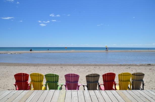 a line of muskoka chairs along the edge of the boardwalk, beach, Lake Ontario