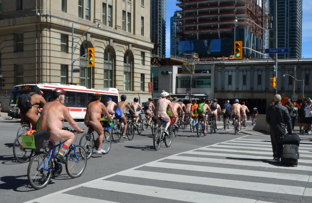 world naked bike ride goes down Bay street, south of Front, a large group of naked people on bicycles
