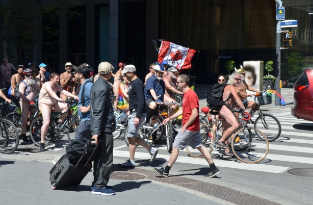 world naked bike ride, a man with a suitcase watches, one nude rider is carrying a Canadian flag