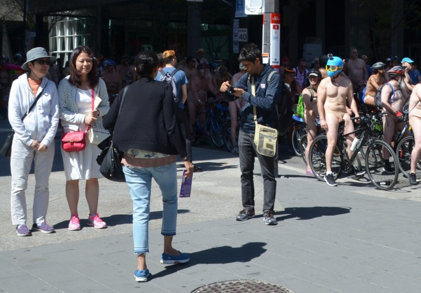 world naked bike ride and people on the sidewalk watching them