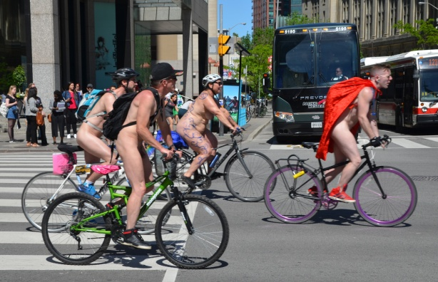 world naked bike ride going down Bay street, crossing Front st and two large buses