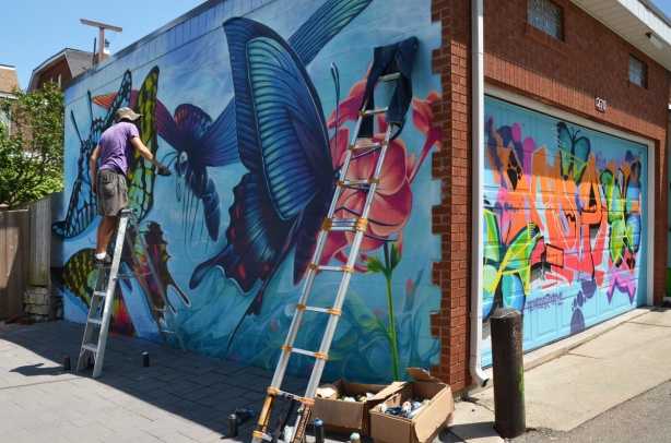 Nick Sweetman on a ladder adding the finishing touches, with spray paint, to a large mural of butterflies on the side of a garage in a lane. Another ladder leans against the same wall, boxes and can of spray paint on the ground. On the same garage, there is a colourful mural on the garage door