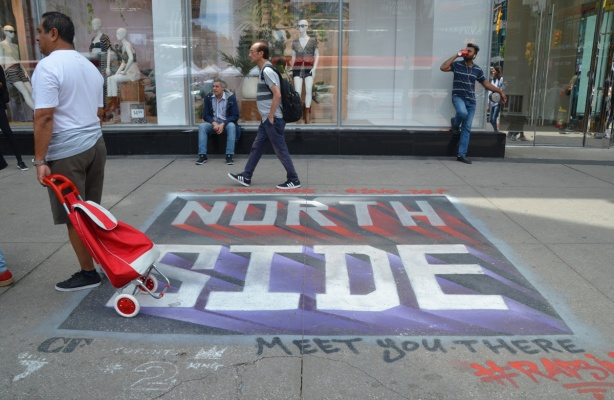 painted on a sidewalk in front of the Eaton Centre, are words North Side, written in Raptors colours, as support for Toronto's basketball team as they play on NBA finals playoffs