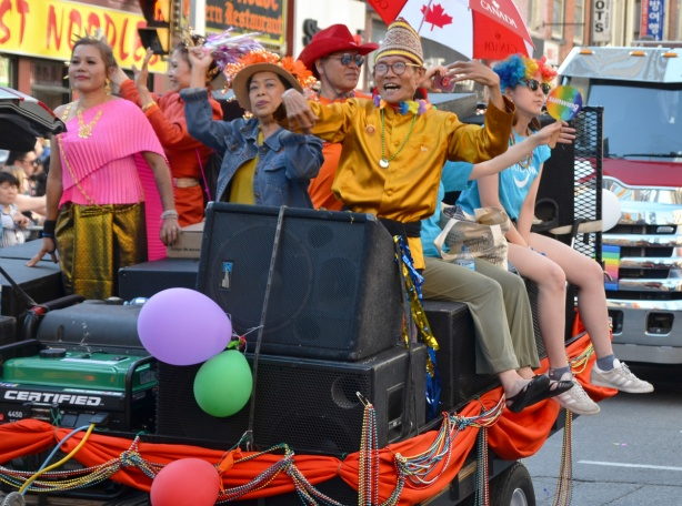 people on a float in a parade, one has a Canada umbrella