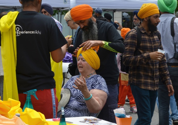 At Turbanup event at Yonge Dundas Square, an older woman is sitting in a chair, talking (gesturing) with her hands while a Sikh man with a long beard and orange turban wraps her head in a pale orange turban