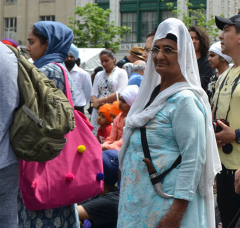 At Turbanup event at Yonge Dundas Square, an older woman with a white cloth over head head and a kirpan sword at her side