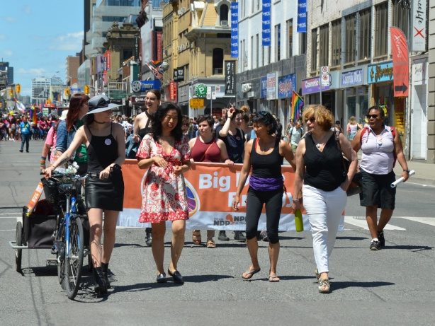 NDP group in dyke march, with orange banner and several women