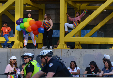 people using a large metal scaffolding structure on a construction project beside Yonge street to sit on to watch pride parade