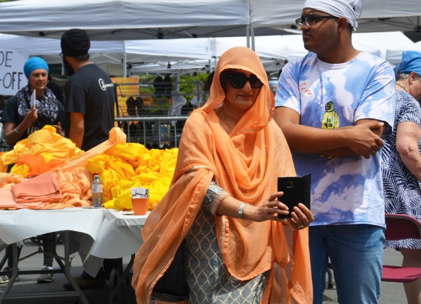 a woman with a light orange cloth draped over her head and around her shoulders and body takes a selfie