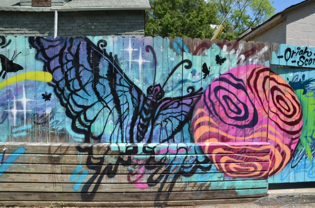 spray painted mural in a lane, butterfly and circle, on wood fence, by Oriah Scott,