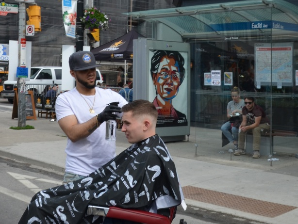 on the street, a man is giving another man a haircut, two people are sitting on a bench in a bus shelter behind, watching