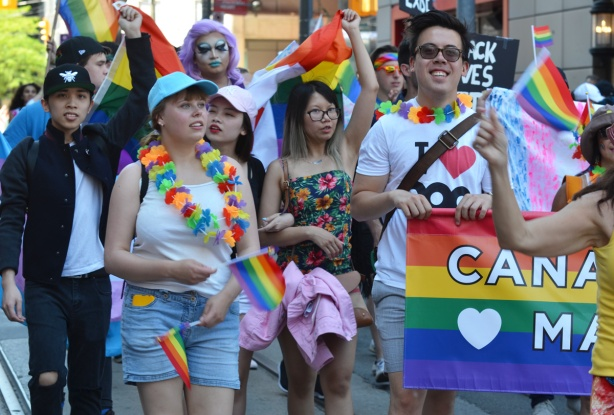 a group of people walking in the pride parade with rainbow flags and accessories