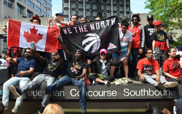 raptors fans with we the north banner and canadian flag sitting on top of entrance to parking lot