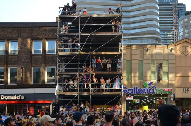 people sitting onscaffolding in the front of a three stprey building on Yonge street, watching the pride parade