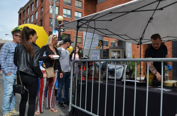 people in a line up to get food at an outdoor vendor, white tent covering,