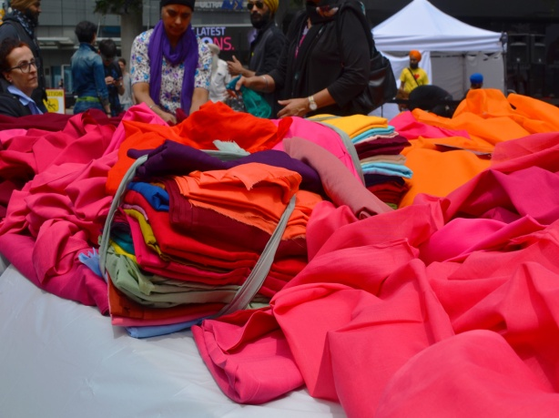 piles of colourful fabric on a table At Turbanup event at Yonge Dundas Square,