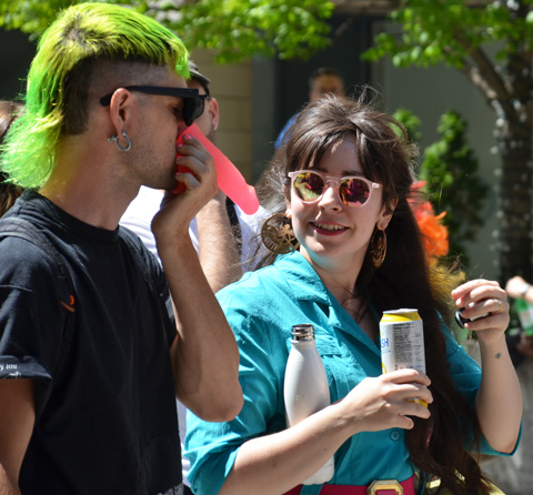 a person in short green hair holds a pink plastic dildo to his nose