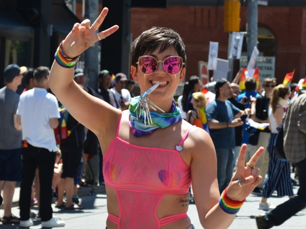 dyke march, woman in pink rimmed glasses holds fingers in peace symbol