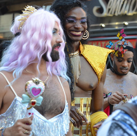 man with beard with pale pink wig and gold crown, another person in a yellow outfit but bare chested