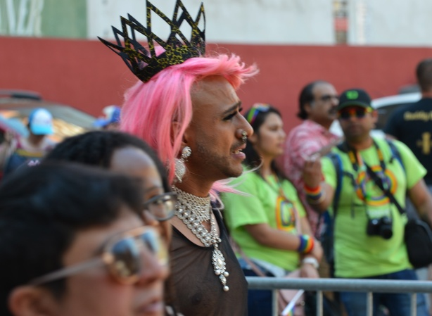 a young man in a pink wig, a fancy necklace, and a crown, walks in a pride parade
