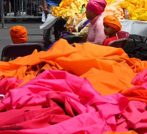 a mother in son in bright turbans, mother in pink and son in orange, sit by a table piled with orange and pink fabric