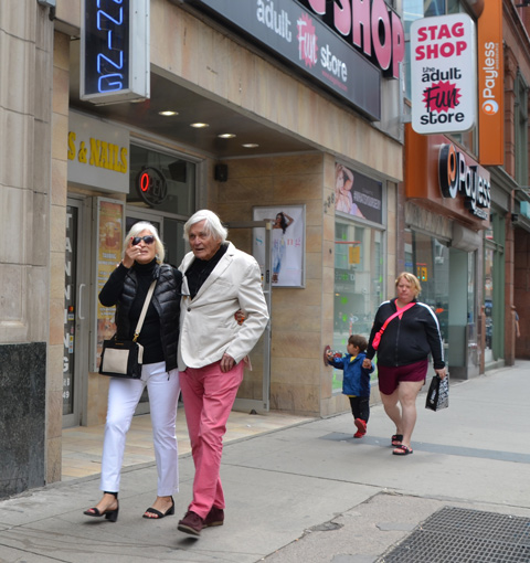 a couple walking together on Yonge, passing the Stag Shop. He is wearing pink pants and a white jacket. Both have white hair.