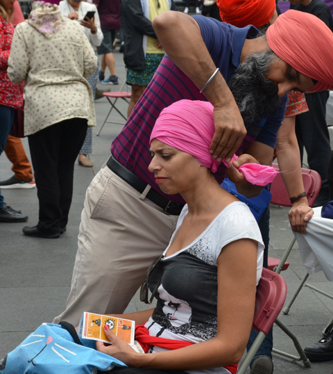 At Turbanup event at Yonge Dundas Square, a sikh man with a pale orange turban wraps a pink turban around the head of a woman who is seated, and frowning