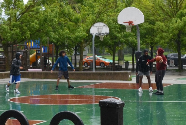 four boys playing basketball on a green and brown court, in the rain,