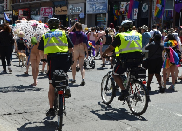 two police on bikes with yellow vests ride in parade behind two people with bare bottoms