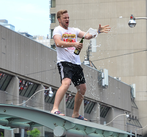 a man in white t shirt and black shorts stands on top of a bus shelter, he has just removed the cork from a bottle of champagne, and the champagne has begun to flow from the bottle