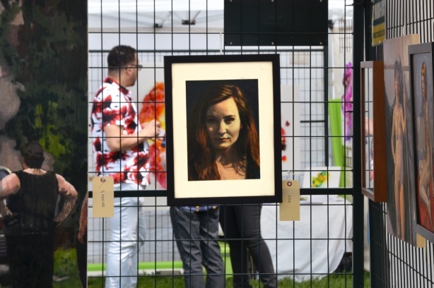 a framed portrait of a woman on a metal grid, people standing behind it including a man with a white shirt with bright red and black blotches