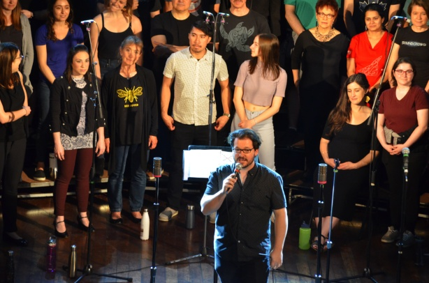 a choir onstage with a man with microphone standing in front of them