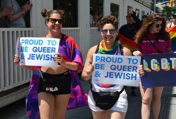 two women in dyke march with signs that say proud to be queer and Jewish