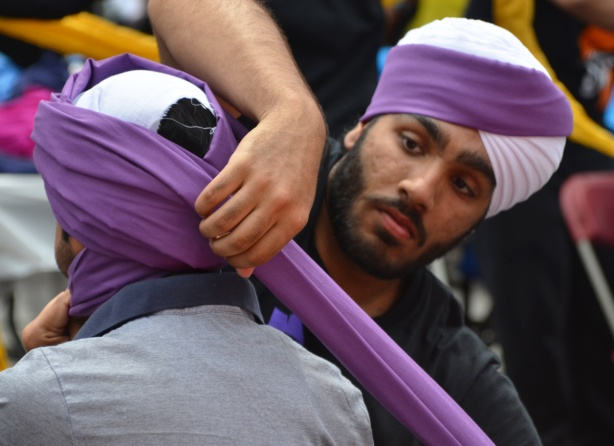 At Turbanup event at Yonge Dundas Square, a man in a purple and white turban wraps another person's head in the same colour of turban