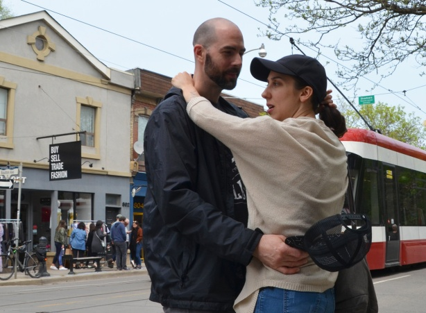 a couple holds each other on the street
