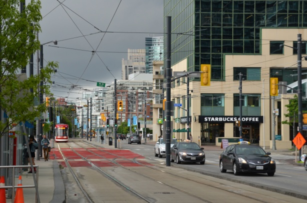 looking west on Queens Quay at Spadina, streetcar tracks, street, trafiic, pedestrian on sidewalk, TTC street car approaching, Starbucks on the corner, low rise buildings in the background