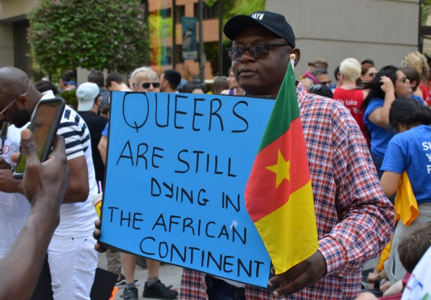 a black man holds a sign that says Queers are still dying in African continent, he is holding a flag from Cameroon