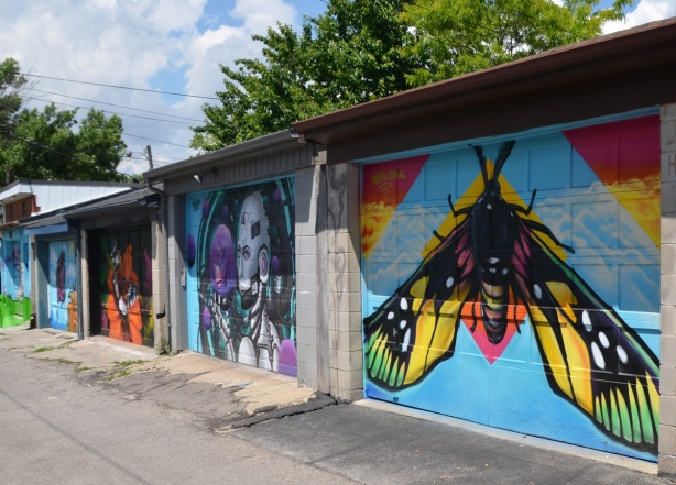butterfly murals painted on garage doors in an alley